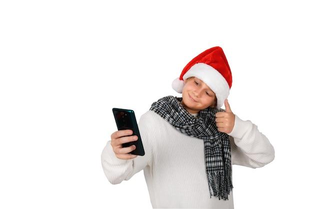 Entzückender lächelnder junge mit rotem weihnachtshut, der selfie nimmt