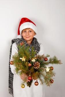 Entzückender lächelnder junge mit rotem weihnachtshut