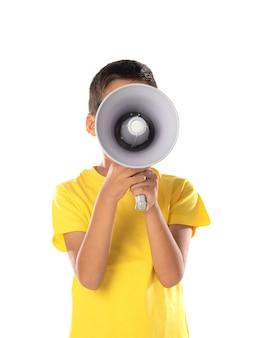 Entzückender lateinamerikanischer junge, der ein gelbes t-shirt mit einem sprechen mit einem megaphon auf weißem hintergrund trägt