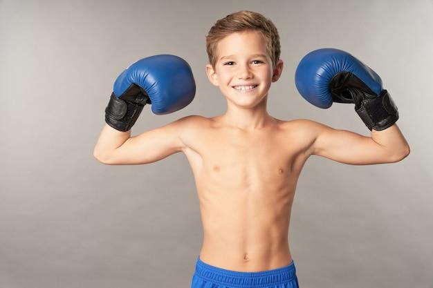 Entzückender männlicher kinderboxer, der in die kamera schaut und lächelt, während er seine bizepsmuskeln demonstriert