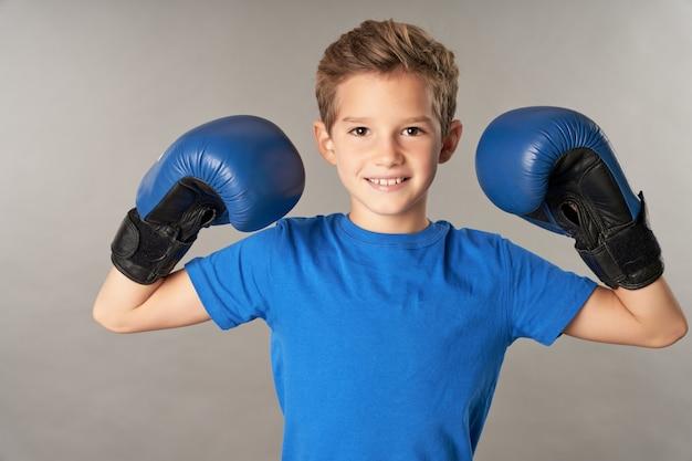 Entzückender männlicher kinderboxer, der sportboxhandschuhe und blaues hemd trägt, während er in die kamera schaut und lächelt