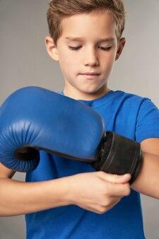 Entzückender männlicher kinderboxer, der vor dem training den boxhandschuh um das handgelenk festzieht