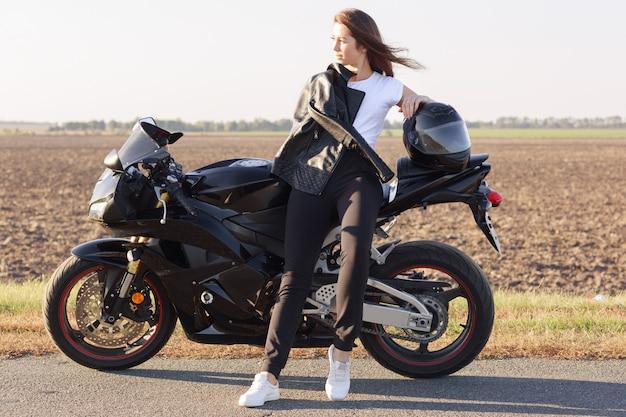 Entzückender magnetischer biker, der reise auf ihrem motorrad hat, in der nähe des feldes steht, herrliche aussichten genießt, beiseite schaut, gute laune hat