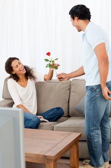 Entzückender mann, der seiner reizenden freundin eine rose im wohnzimmer gibt