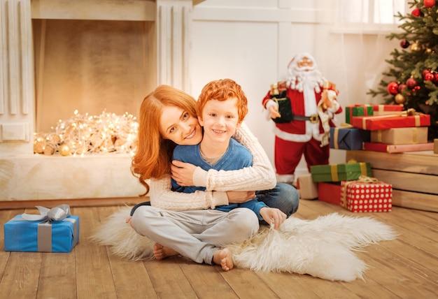 Entzückender moment der reifen dame, die lächelt, während sie ihren entzückenden sohn fest umarmt und familienzeit mit ihm genießt.