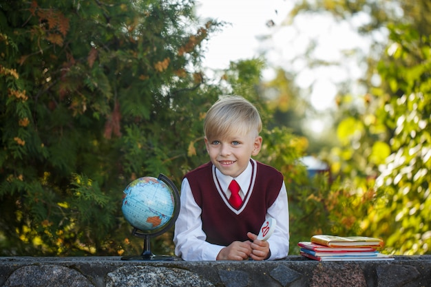 Entzückender schüler mit büchern und kugel an draußen. bildung für kinder. zurück zum schulkonzept.