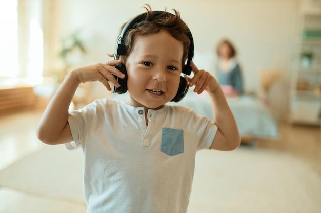Entzückender süßer kleiner junge, der drahtlose kopfhörer trägt und musik hört