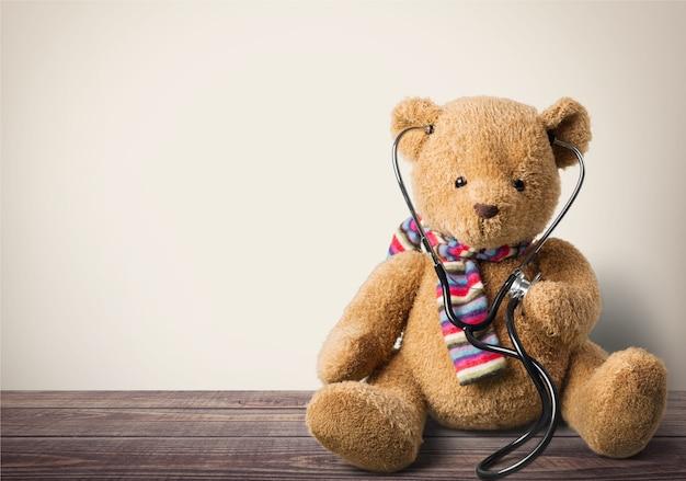 Entzückender teddybär, der ein stethoskop hält., isoliert