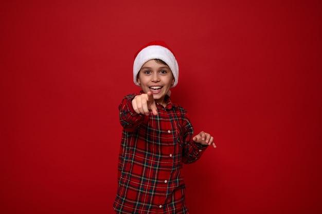Entzückender vorpubertärer junge in rot kariertem hemd, der eine weihnachtsmütze trägt, zeigt direkt auf die kamera, lächelt mit einem schönen zahnigen lächeln, das vor farbigem hintergrund mit kopienraum für weihnachtswerbung posiert