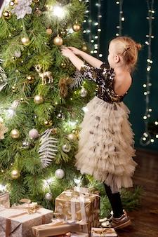 Entzückender weihnachtsbaum des kleinen mädchens zu hause. nettes kind, das sich nach hause für weihnachtsfeier vorbereitet. weihnachts- und neujahrsfeier.