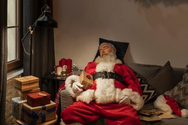 Entzückender weihnachtsmann, der ein schläfchen hält