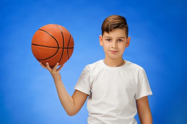 Entzückendes 11 jahre altes jungenkind mit basketballball