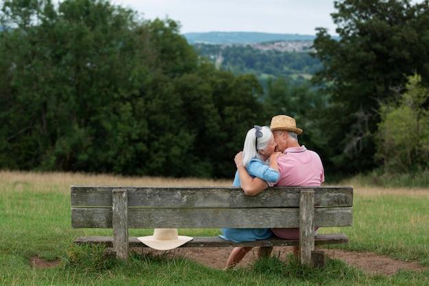 Entzückendes älteres paar, das auf einer bank sitzt