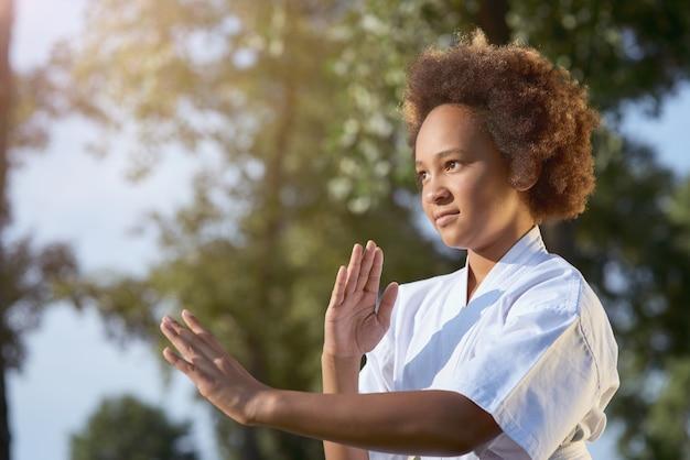 Entzückendes afroamerikanisches mädchen, das karate auf der straße praktiziert