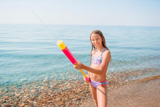 Entzückendes aktives kleines mädchen am strand während der sommerferien