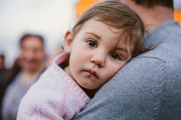Entzückendes armenisches kind, das ihren vater in der straße umarmt