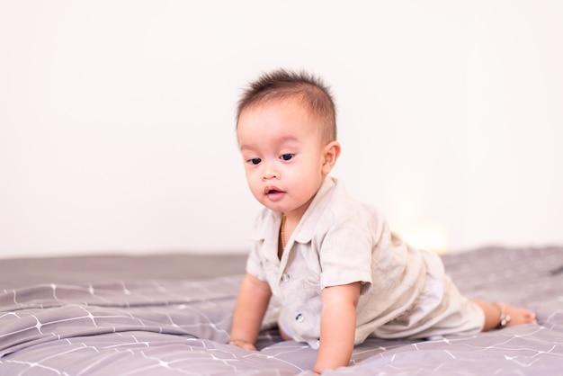Entzückendes asiatisches baby krabbelt auf dem bett, glückliches und lustiges neugeborenes kind