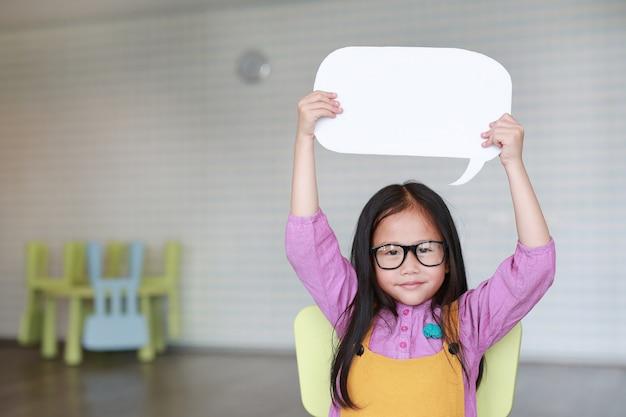 Entzückendes asiatisches kleines mädchen, das leere leere spracheblase hält, um etwas im klassenzimmer mit der kamera gerade lächeln und betrachten zu sagen. bildungs- und gesprächskonzept.