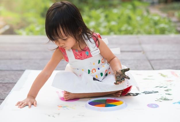 Entzückendes asiatisches kleines mädchen spielt durch farbmalerei im garten außerhalb des hauses.