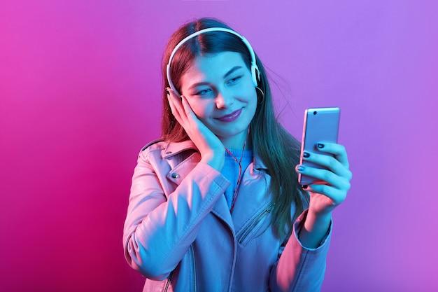 Entzückendes attraktives junges mädchen, das musik in kopfhörern lokalisiert über rosa neonraum hört, berührt ihr ohr und schaut auf smartphone-bildschirm