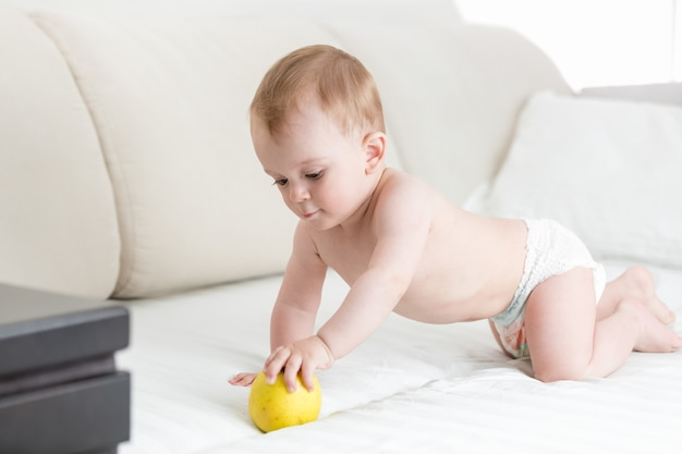 Entzückendes baby, das auf dem bett krabbelt und nach apfel greift