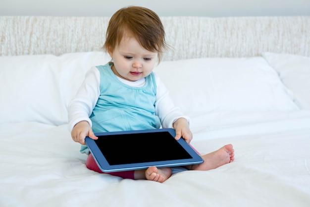 Entzückendes baby, das auf einem bett hält ein computertablett sitzt