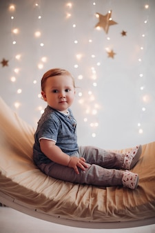 Entzückendes baby, das auf schöner schaukel sitzt, die für weihnachten verziert wird.
