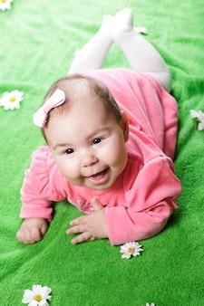 Entzückendes baby, das auf wiese liegt und lächelt
