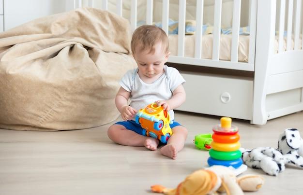 Entzückendes baby, das mit buntem spielzeugauto auf dem boden sitzt