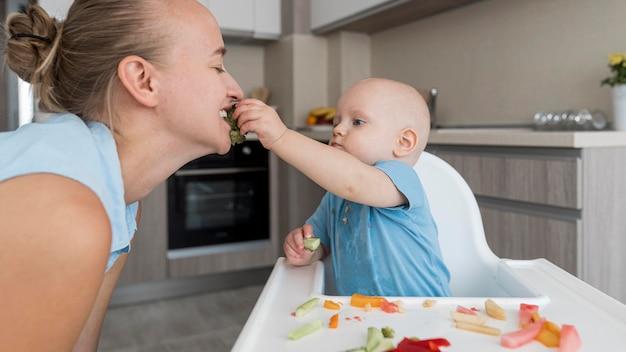 Entzückendes baby, das mit essen spielt