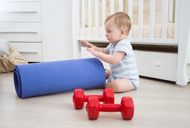 Entzückendes baby, das mit hanteln und fitnessmatte spielt