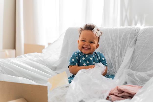 Entzückendes baby, das vor dem auszug in ihrem alten haus sitzt