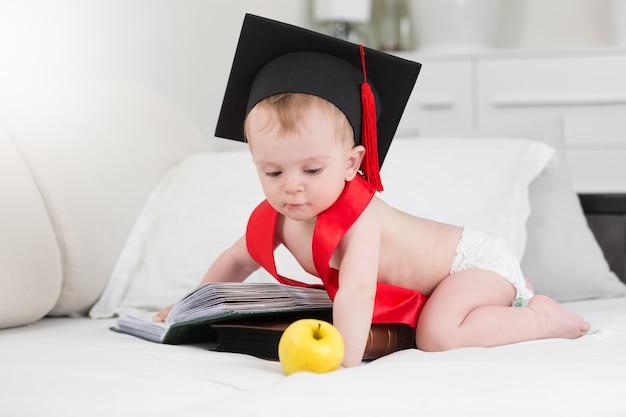 Entzückendes baby in abschlusskappe posiert mit apfel und großem buch