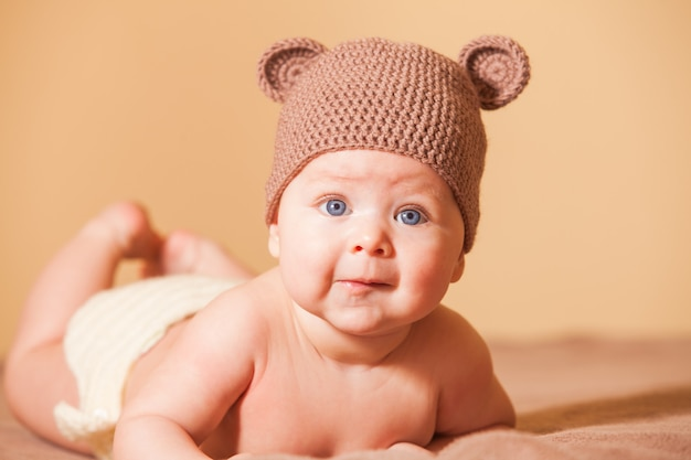 Entzückendes baby mit bärenmütze auf dem bett liegend