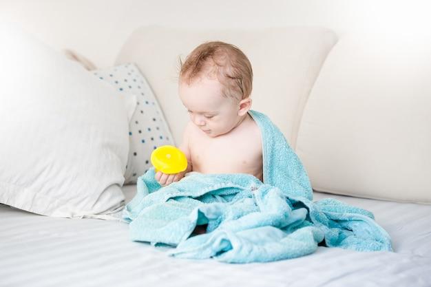 Entzückendes baby mit blauem handtuch bedeckt, das nach dem baden mit gelber gummiente auf dem sofa spielt