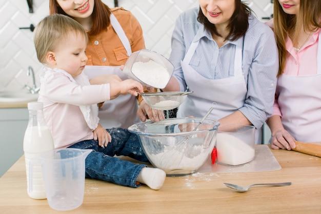 Entzückendes baby mit mutter, tante und großmutter, die teig zu hause mit mehl und ei und zucker zusammen machen. frauen in weißen schürzen und kochmützen streuen teig für gebäck mit mehl auf tisch