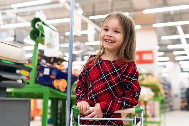 Entzückendes babykind mit wagen, der frisches gemüse im örtlichen geschäft wählt. verkauf, konsumismus und menschenkonzept - glückliches kleines mädchen mit essen im einkaufswagen am lebensmittelgeschäft