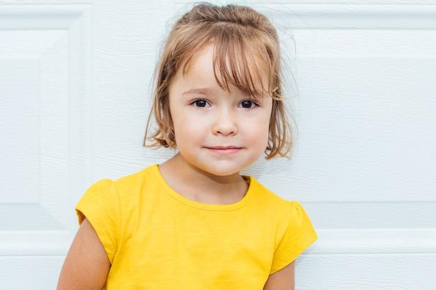 Entzückendes blondes mädchen, das ein gelbes hemd trägt, das gegen weißen hintergrund lehnt