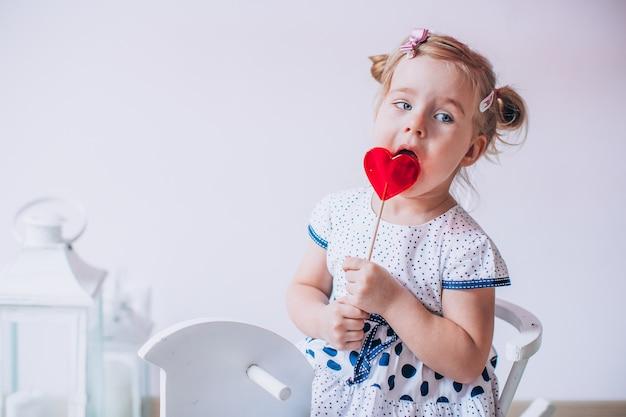 Entzückendes blondes mädchen, das einen karamell-lollypop in der form eines herzens isst. kind sitzt auf einem weißen holzpferd