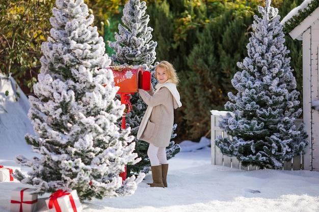 Entzückendes blondes mädchen, das ihren brief an sankt, weihnachtszeit sendet