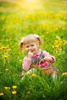 Entzückendes blondes mädchen, das im gras mit korb und dem lächeln sitzt