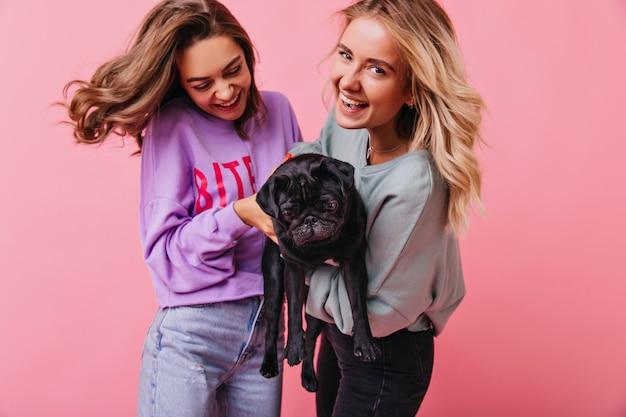 Entzückendes blondes mädchen, das mit ihrer schwester und französische bulldogge aufwirft. lächelnde junge damen, die spaß mit ihrem haustier haben.