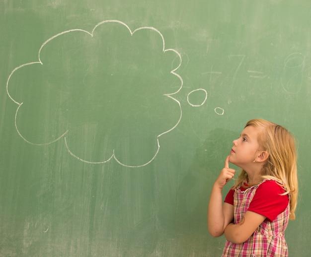Entzückendes blondes mädchen der kleinen schule im schulklassenzimmer an bord, das mit wolke für kopienraum aufwirft