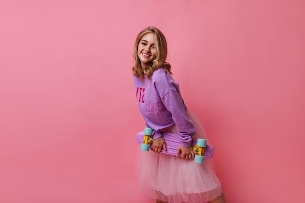 Entzückendes blondes mädchen im lila hemd, das aufwirft. blithesome lockiges weibliches modell im weißen rock, der skateboard hält.