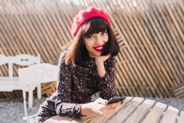 Entzückendes dunkelhaariges mädchen, das auf freunde im stilvollen straßencafé wartet und neue nachrichten auf schwarzem telefon prüft. lächelnde brünette junge frau mit französischem vintage-outfit, das im open-air-restaurant ruht