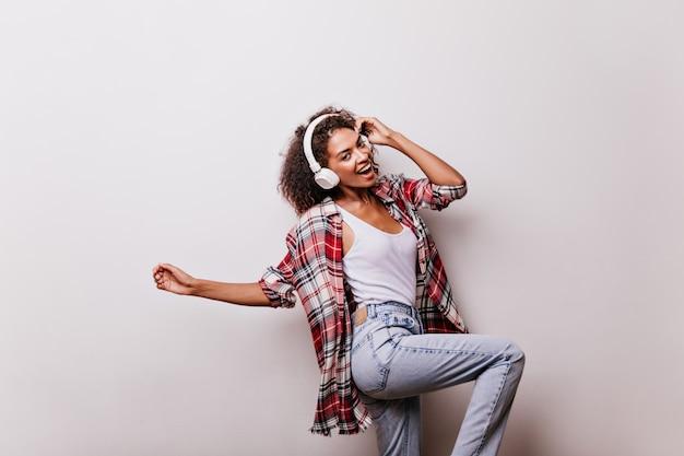 Entzückendes dunkelhaariges mädchen, das tanzt, während es auf beige posiert. afrikanisches weibliches modell trägt kopfhörer und rotes hemd