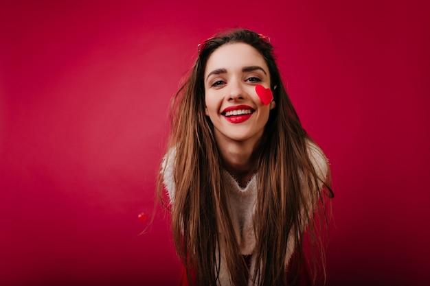 Entzückendes europäisches mädchen mit langen haaren, die glück am valentinstag ausdrücken