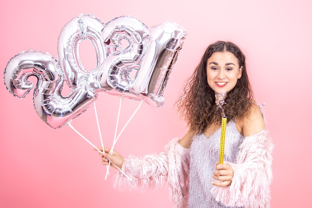 Entzückendes festlich gekleidetes brünettes mädchen mit lockigem haar auf einer rosa wand betrachtet eine ausgelöschte feuerwerkskerze mit silbernen luftballons für das neujahrskonzept