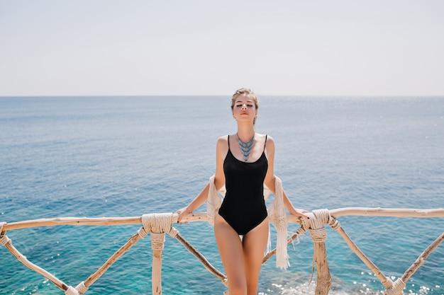 Entzückendes formschönes mädchen in der trendigen schwarzen badebekleidung, die gerne mit ozeanlandschaft aufwirft. schlanke wunderschöne frau in der stilvollen halskette, die mit geschlossenen augen steht und frisches meeresaroma in sonnigem tag genießt