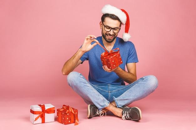Entzückendes foto des attraktiven jungen mannes im weihnachtshut mit dem schönen lächeln, das geburtstagsgeschenkboxen lokalisiert über rosa wand hält, die auf dem boden sitzt. geschenkkonzept.